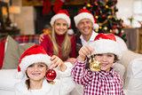 Cute little siblings wearing santa hat holding baubles