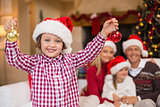 Son wearing santa hat holding baubles in front of his family