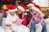 Festive family wearing santa hat while reading on the couch