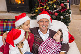 Festive family in santa hat hugging on couch