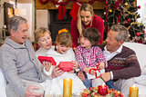 Multi generation family opening presents on sofa