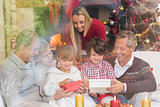 Multi generation family opening presents on sofa