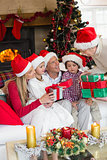 Family wearing christmas hat while holding presents