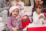 Festive little siblings opening gifts