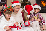 Happy extended family opening gifts on the couch