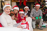 Portrait of a happy extended family in santa hat holding gifts