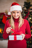 Smiling woman in santa hat opening a gift