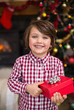 Festive little boy holding a gift