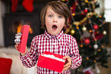 Surprised little boy holding a gift