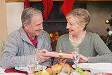 Senior man offering a christmas present to his wife