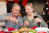 Man carving chicken while his wife drinking red wine