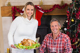 Couple smiling at camera while woman holding roast turkey