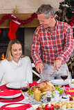 Man carving chicken during christmas dinner