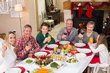 Smiling family toasting to camera during christmas dinner