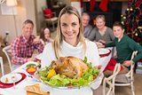 Pretty woman showing the roast turkey in front of her family