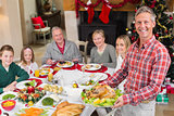 Man holding turkey roast with family at dining table