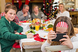 Little girl holding smartphone during christmas dinner