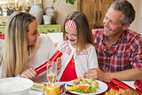 Little girl pulling a christmas cracker with their parents