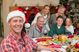 Smiling father in santa hat posing in front of his family