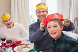 Smiling father putting party hat on sons head