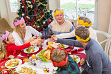 Family in party hat toasting at christmas dinner