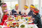 Grandfather in party hat carving chicken during dinner