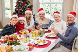 Smiling family in santa hat toasting to camera