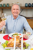 Smiling man toasting at christmas dinner