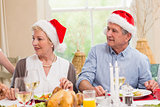 Cute mature couple in santa hat at christmas dinner