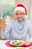 Pretty young woman in santa hat toasting with white wine