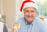 Smiling mature man in santa hat toasting with white wine