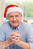 Portrait of mature man in santa hat with hands together