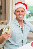 Handsome man in santa hat toasting with white wine