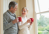 Senior couple holding red mugs