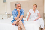 Senior couple not speaking after an argument on bed