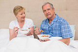 Senior couple having breakfast in bed