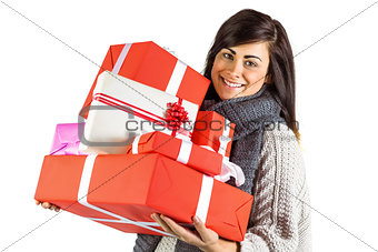 Smiling brunette holding pile of gifts