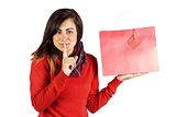 Brunette holding gift bag and keeping a secret