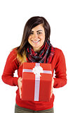 Smiling brunette showing a gift with white bow