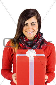 Smiling brunette holding a gift with white bow