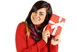 Excited brunette holding red gift
