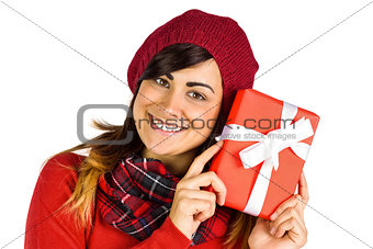 Smiling brunette in red hat holding gift