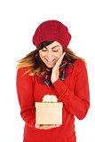 Surprised brunette holding a gift