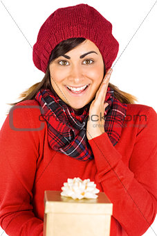 Astonished brunette holding a gift