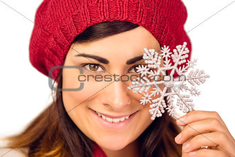 Smiling brunette in hat holding snowflake