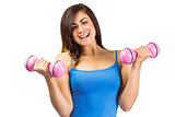Smiling fit brunette holding dumbbells