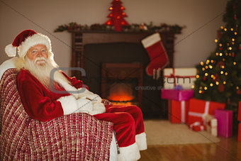 Festive santa claus sitting on couch at christmas