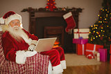 Santa using laptop on the couch at christmas
