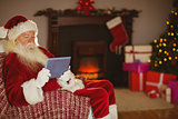 Santa using tablet on the couch at christmas