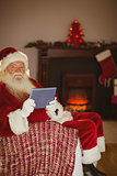 Smiling santa using tablet on the couch